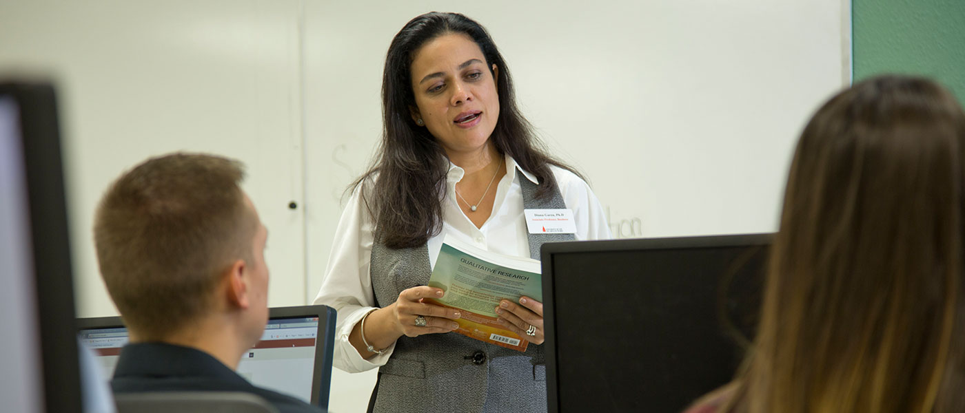 Female faculty member teaching a classroom on computers.