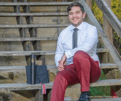 Graduation photo of Justin Clark sitting on the steps.